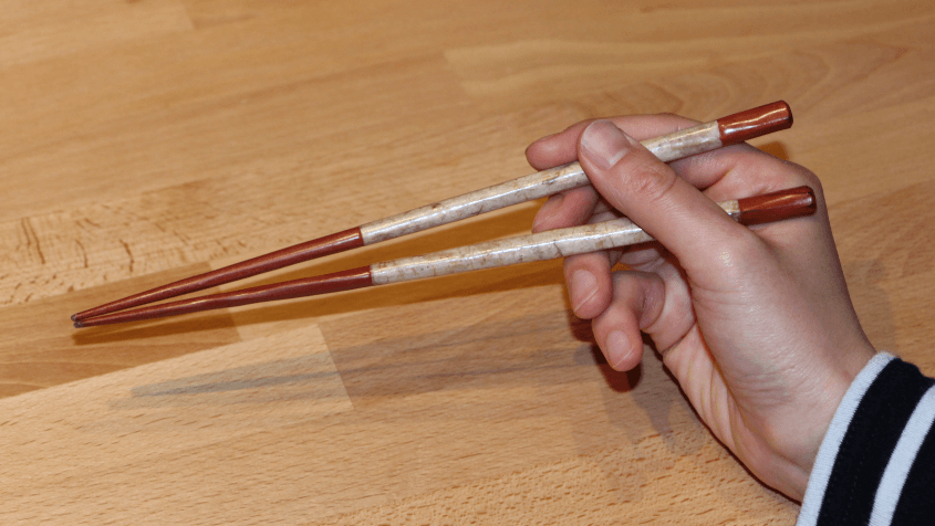 The upper chopstick is placed with its rear at the base of the index finger and with its middle just bellow the fingernail of the middle finger. The top of the thumb fixates it.
